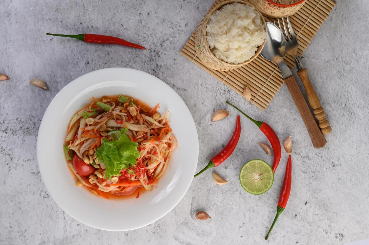 Salade de papaye thaï sur une assiette blanche avec riz gluant, piment, cuillère et fourchette photo