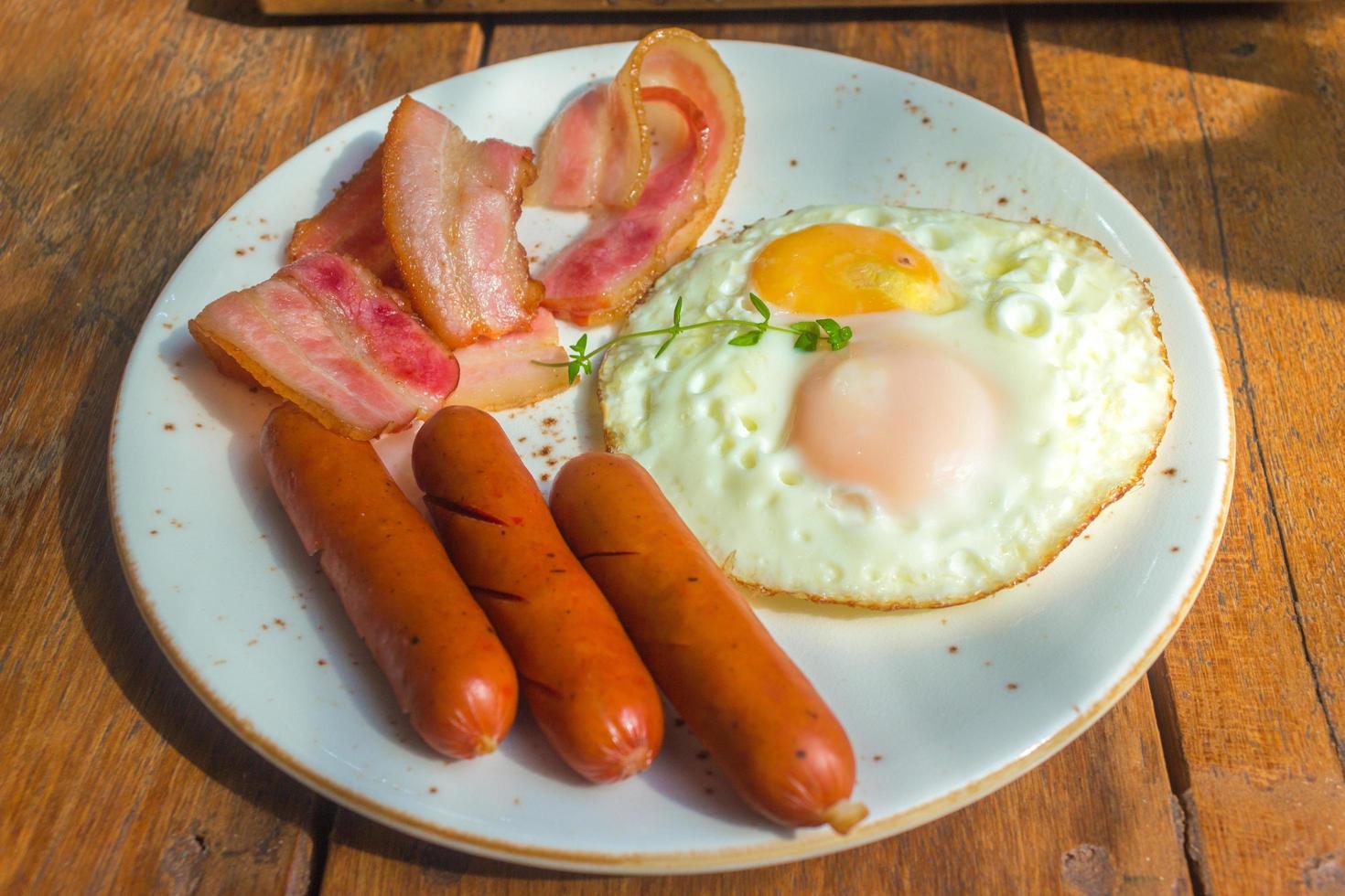 bacon, œufs au plat et saucisses sur plaque blanche et table en bois photo