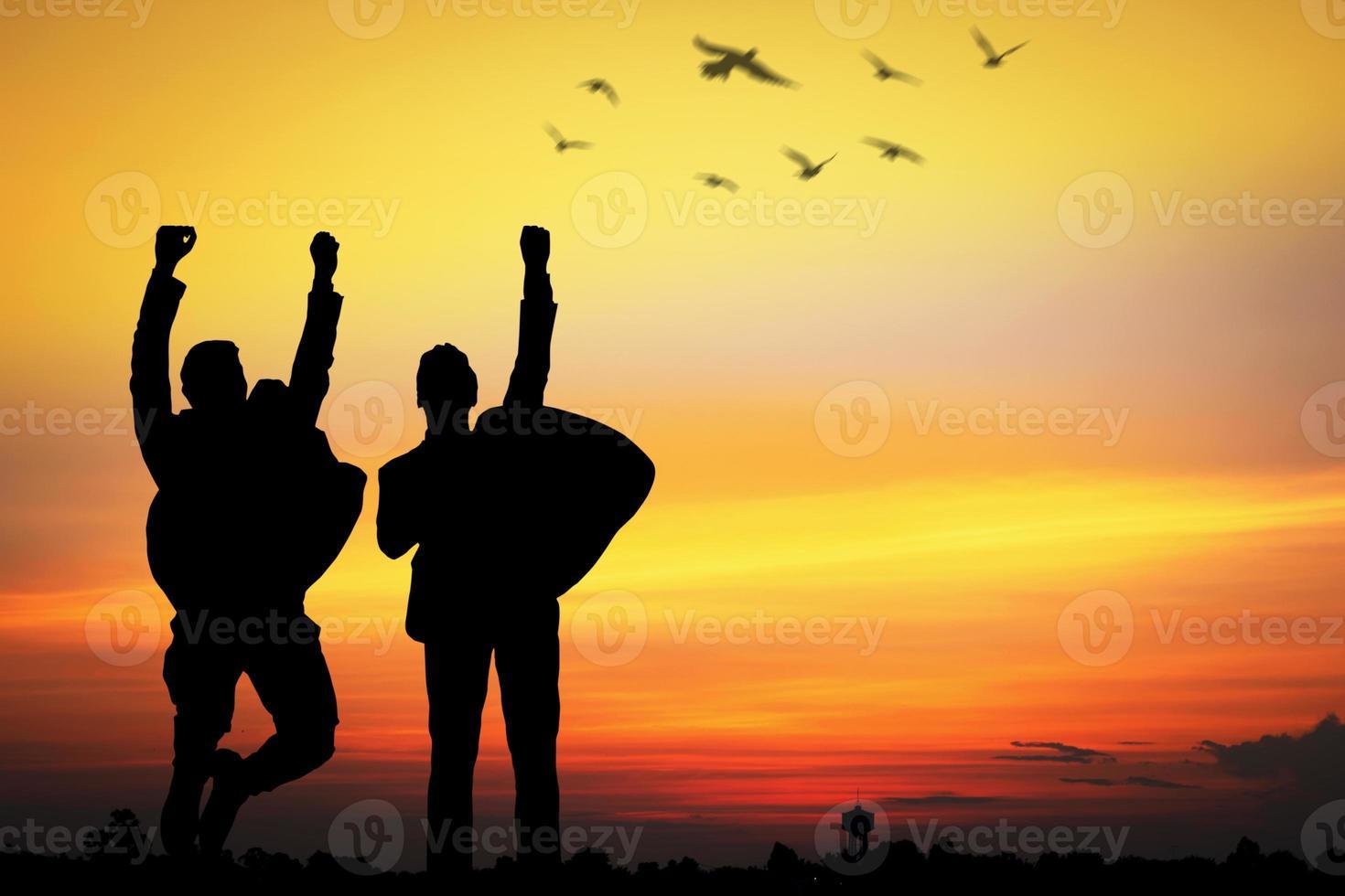 silhouette de personnes acclamant au coucher du soleil photo