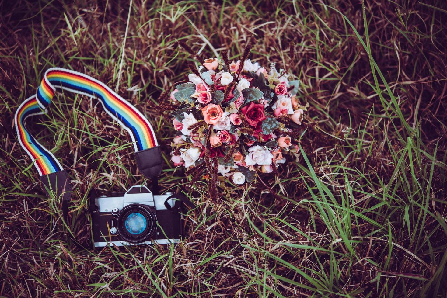Appareil photo vintage avec bouquet de fleurs sur fond d'herbe