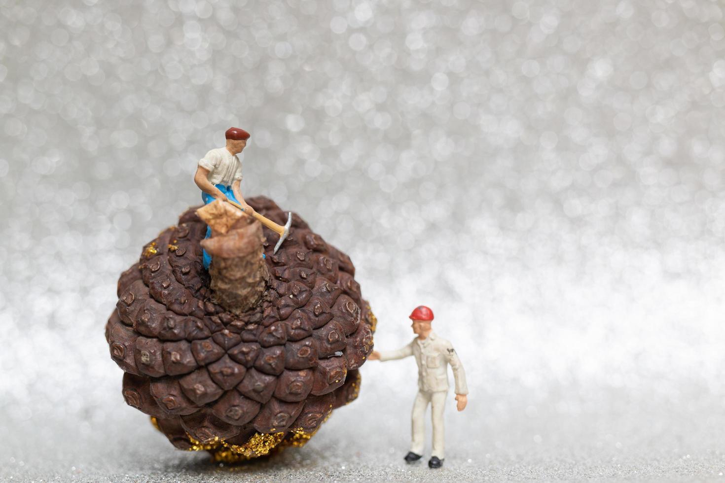 Figures miniatures d'une équipe travaillant sur une pomme de pin de Noël photo