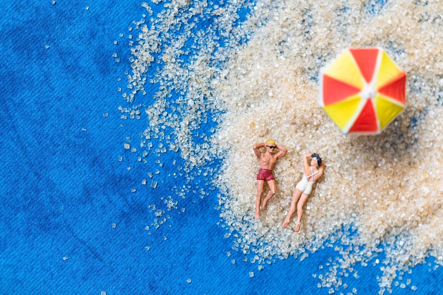 figurines miniatures assis sur la plage photo