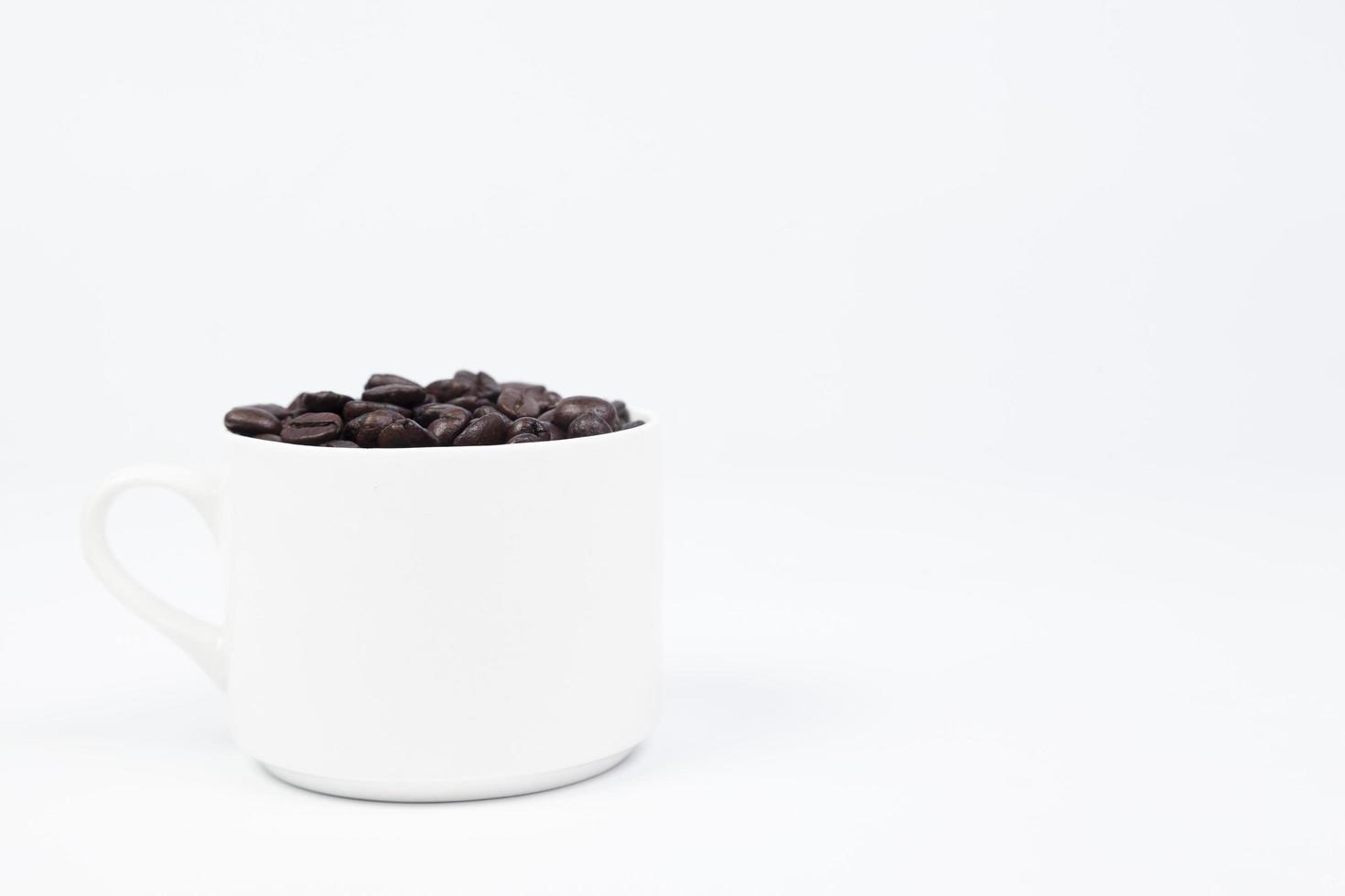 tasse avec des grains de café sur fond blanc photo