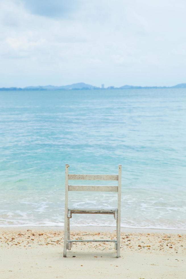 chaise en bois blanche à la mer photo