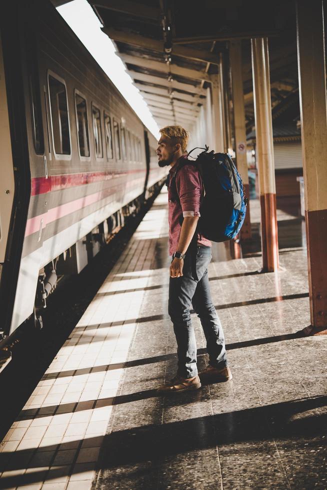 jeune touriste hipster avec sac à dos à la gare photo