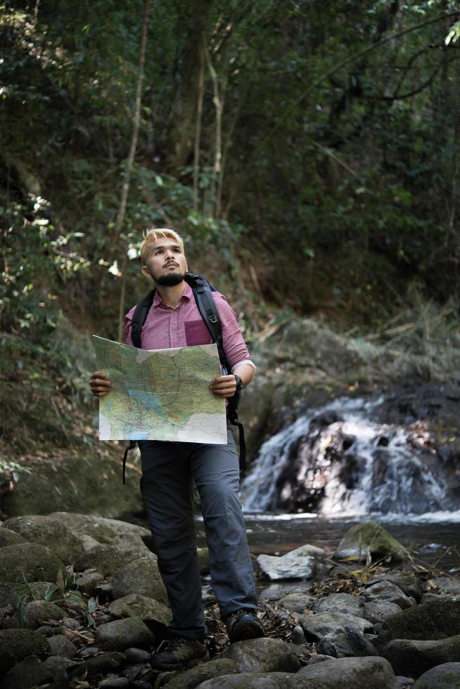 aventure homme observant la carte sur un chemin de montagne photo