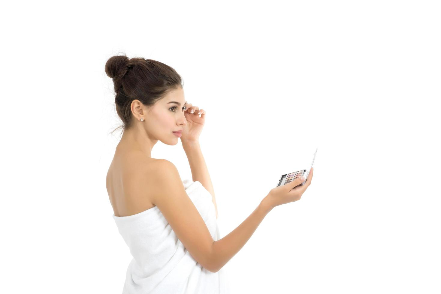 belle femme tenant le maquillage isolé sur fond blanc photo