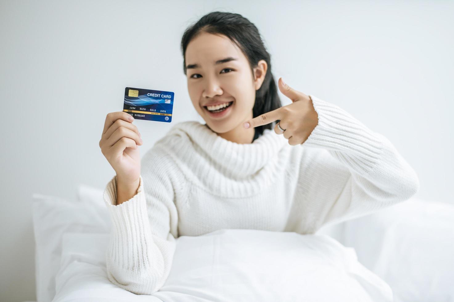 jeune femme, à, a, carte crédit, sourire, lit photo