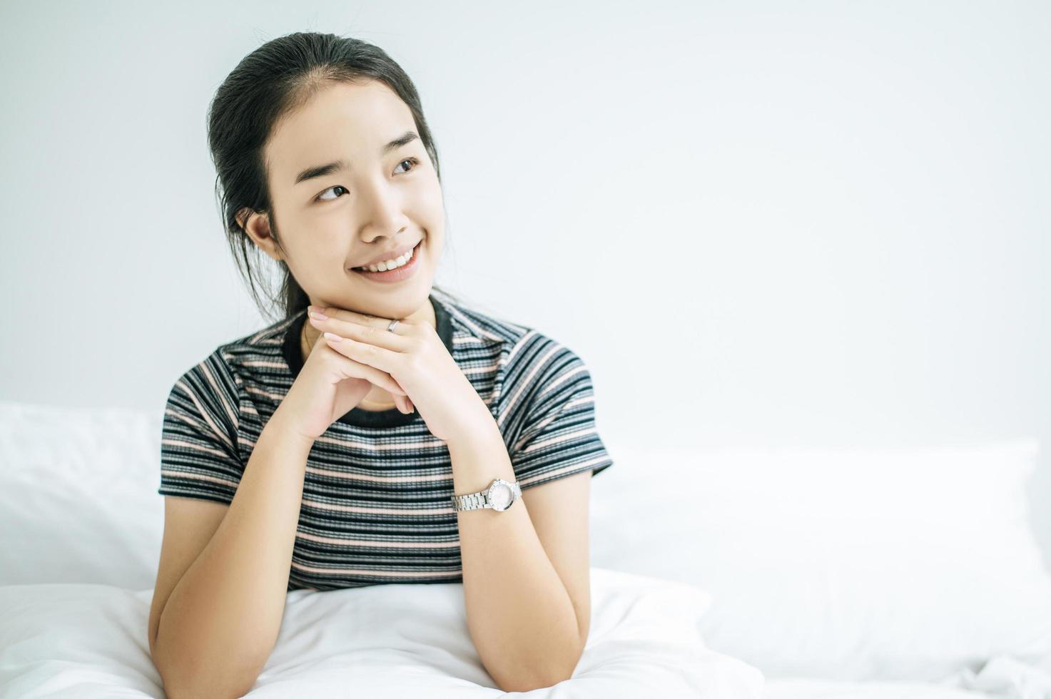 une femme est assise avec ses mains posées sous le menton et sourit photo