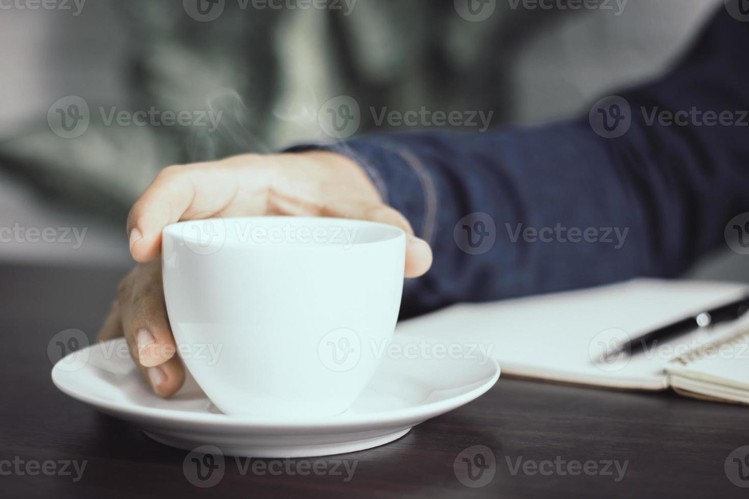 main tenant une tasse de café photo