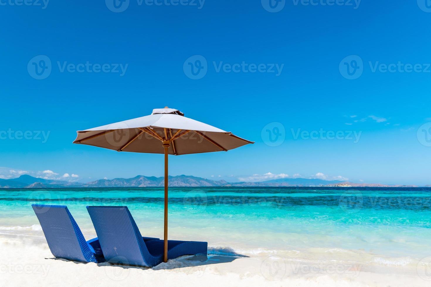 transats avec parasol sur la plage de sable photo