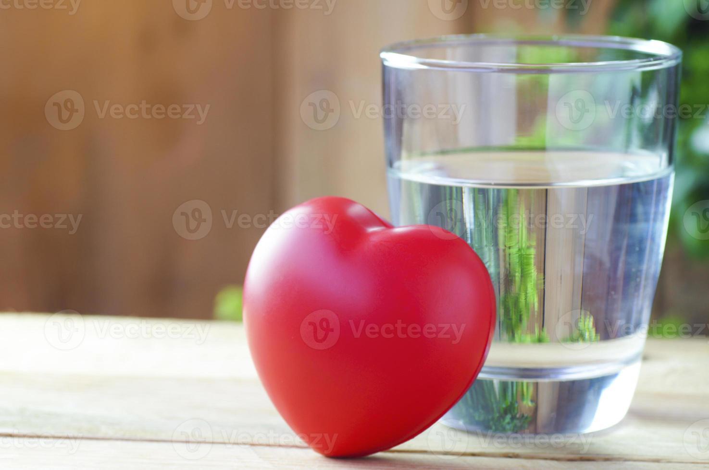 Coeur rouge avec un verre d'eau sur fond de bois photo