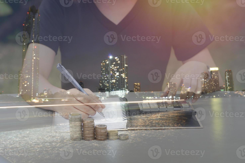 Double exposition de personne qui écrit sur table avec pile de pièces et ville de nuit photo