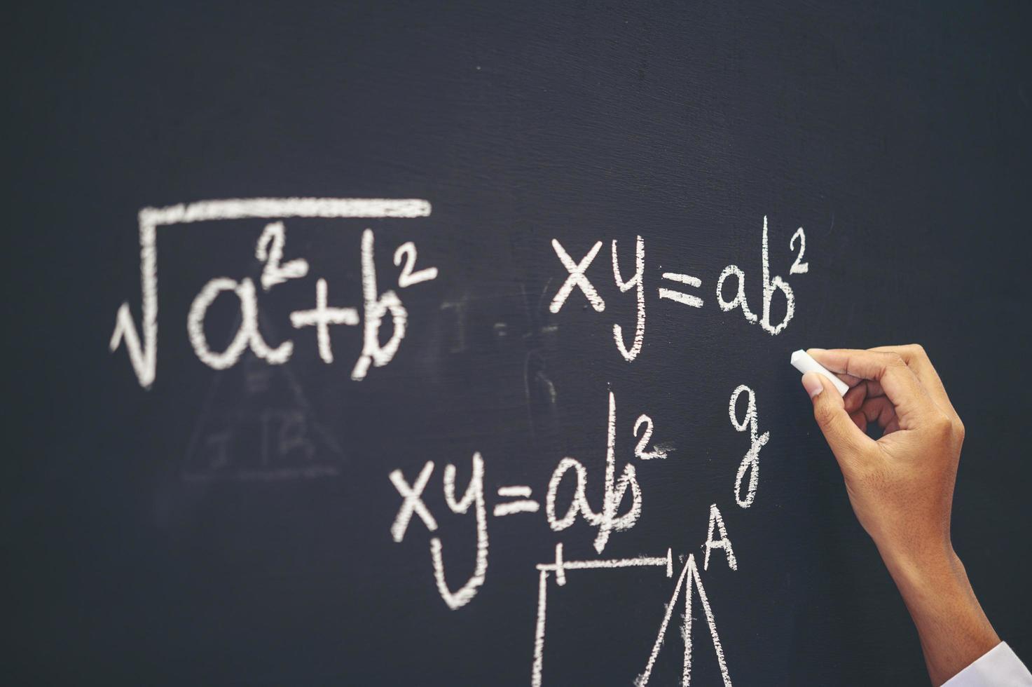 L'élève écrit la formule à la craie blanche sur le tableau noir photo