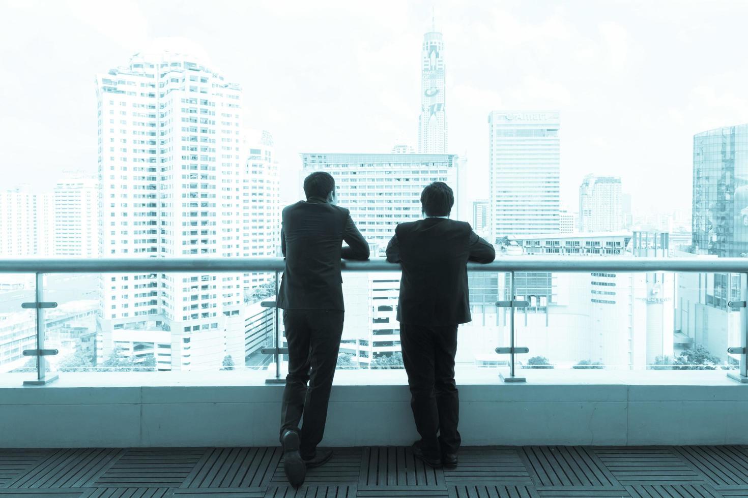 deux hommes d'affaires parlant sur un toit et regardant la ville. photo