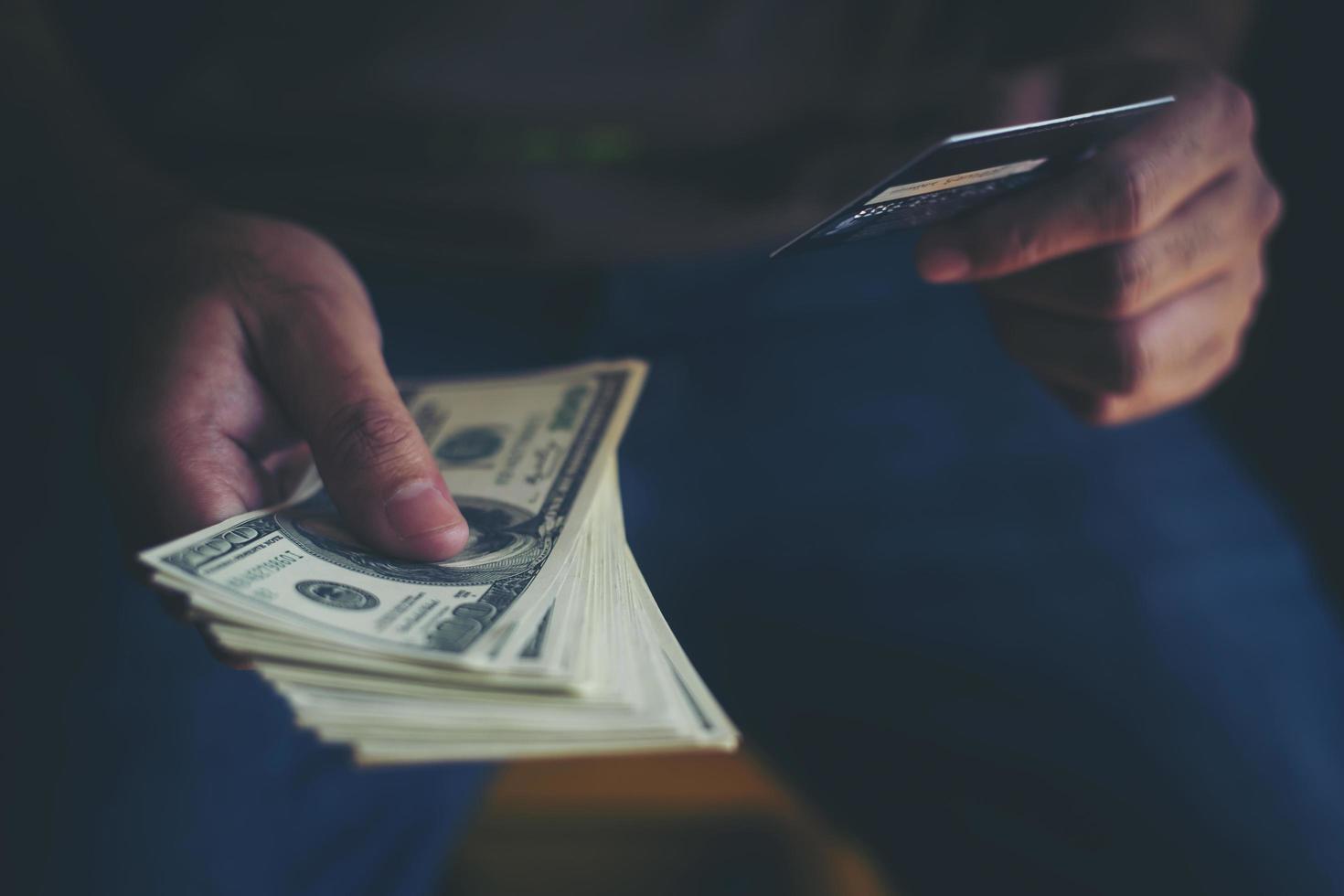 mains tenant des dollars avec carte de crédit pour faire des achats en ligne photo