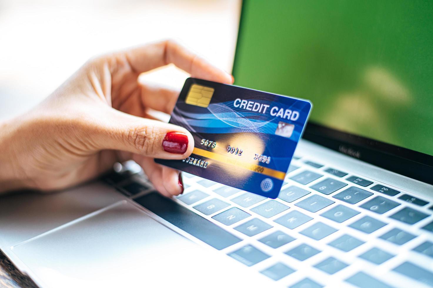femme avec un ordinateur portable et une carte de crédit photo