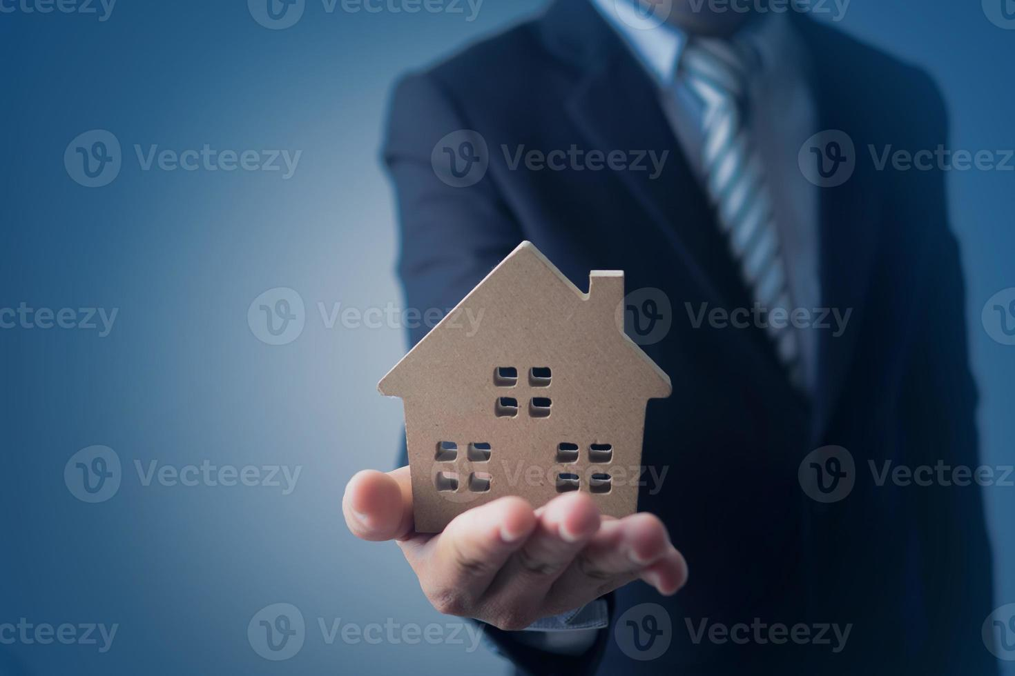 modèle de maison d'homme d'affaires sur fond bleu foncé photo