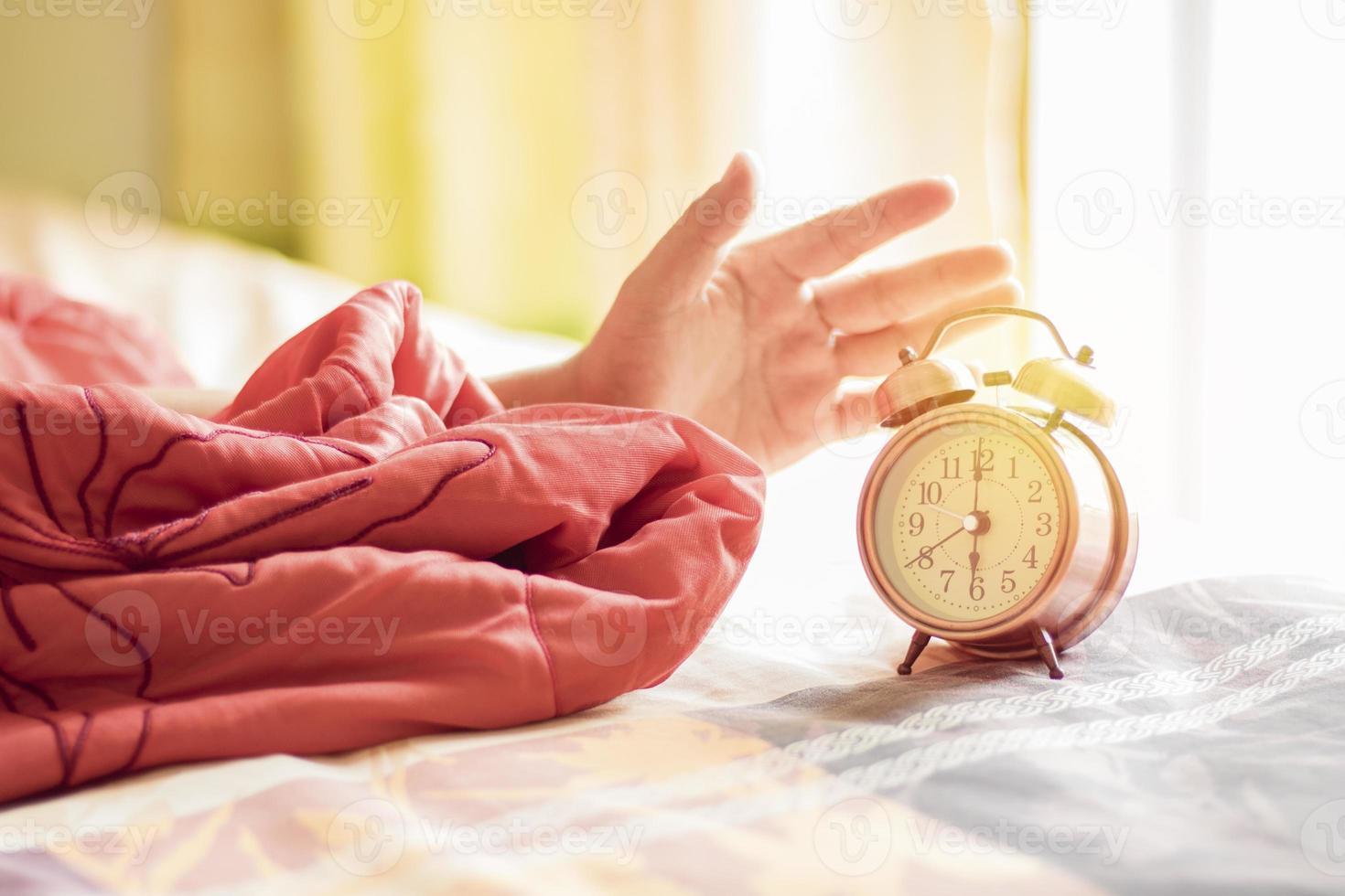 réveil main arrêtant sur le lit à 6 heures photo