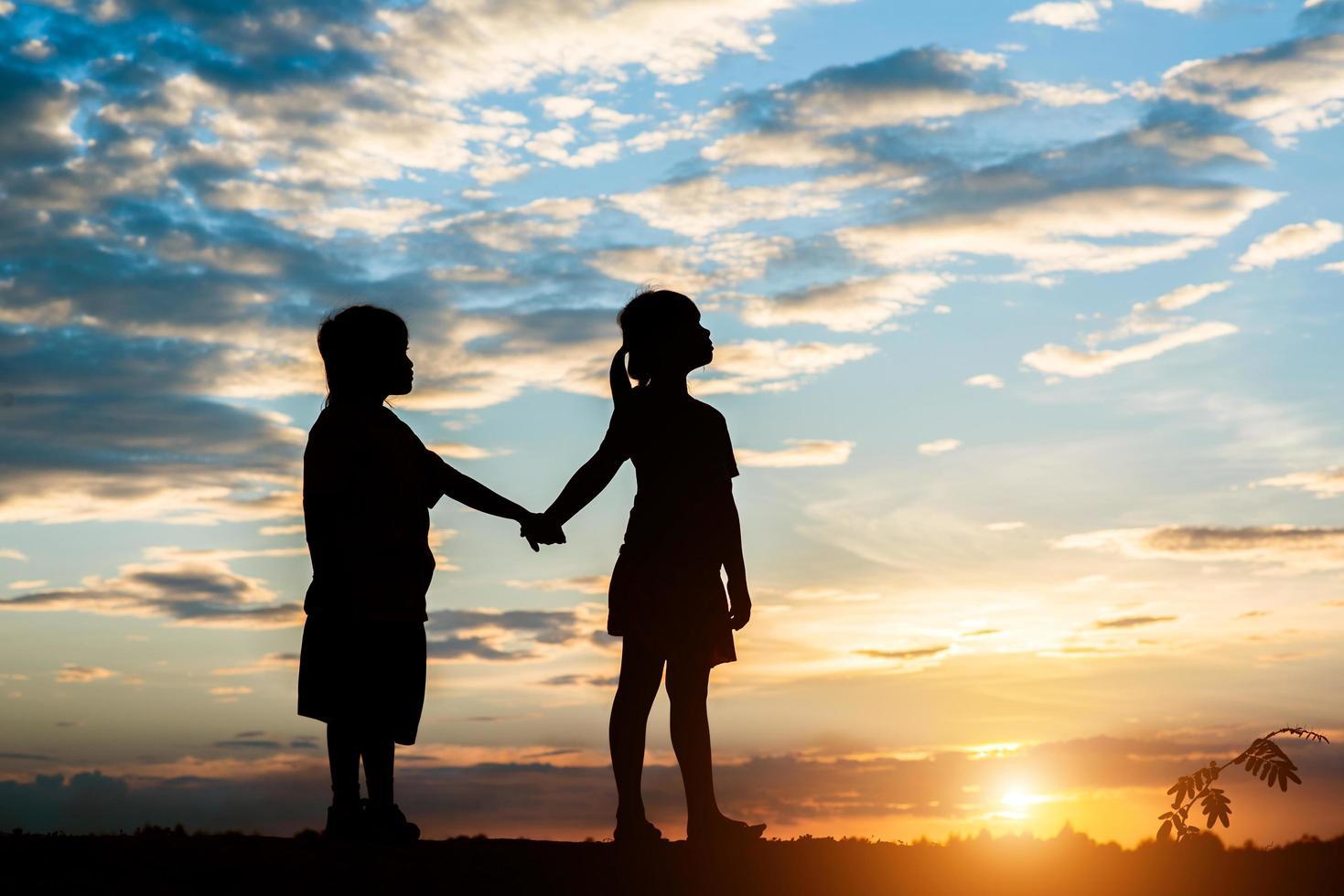 coucher de soleil silhouette d'enfants jouant photo