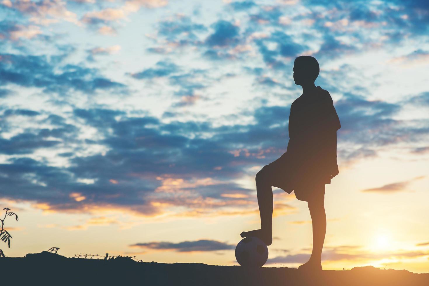 silhouette d'enfants jouant au football photo
