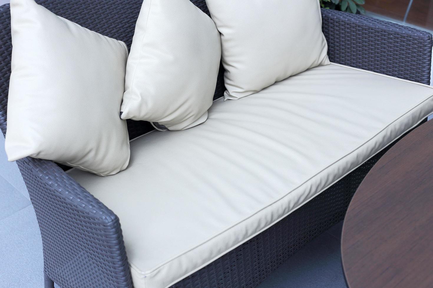 Oreillers décoratifs blancs sur un canapé en bois dans le salon photo