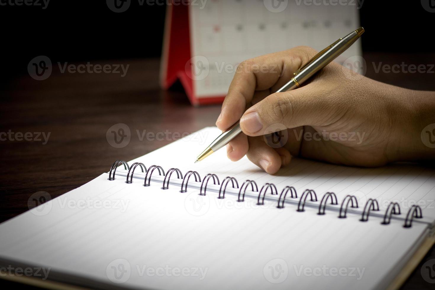 Main qui écrit sur un ordinateur portable dans un ton sombre photo
