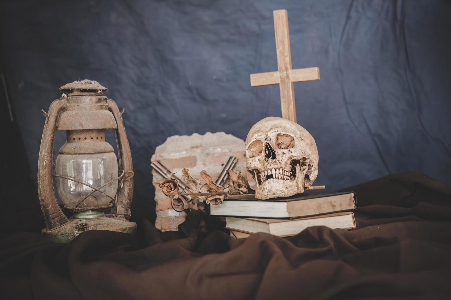 Nature morte avec des crânes sur des livres, de vieilles lampes, des fleurs sèches et des fusils croisés photo