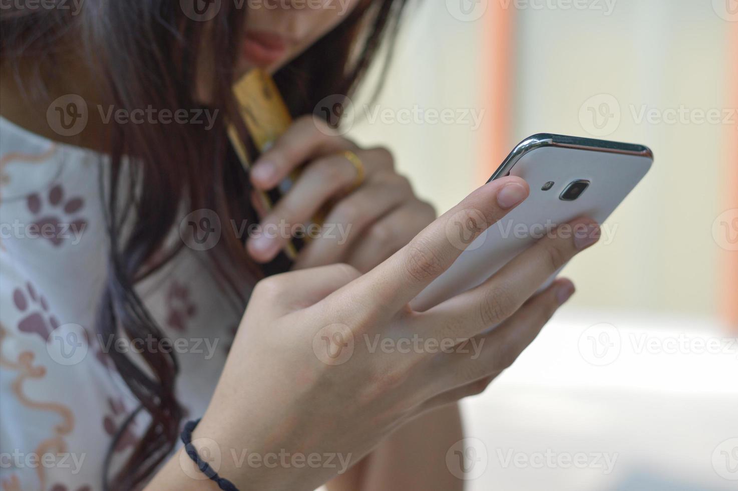 femme utilisant un smartphone pour acheter en ligne avec carte de crédit photo