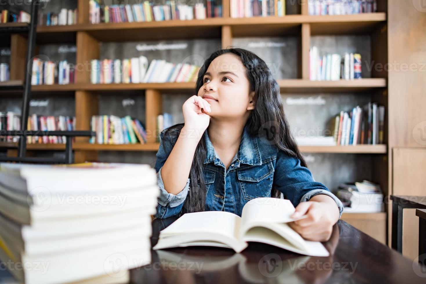 Young woman reading book assis à l'intérieur dans un café urbain photo