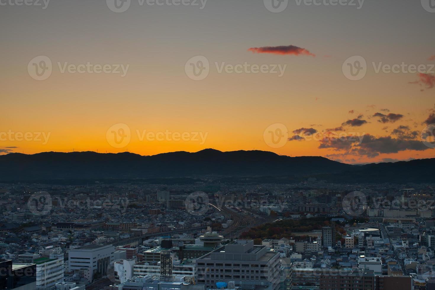 lever du soleil sur une ville avec des montagnes photo