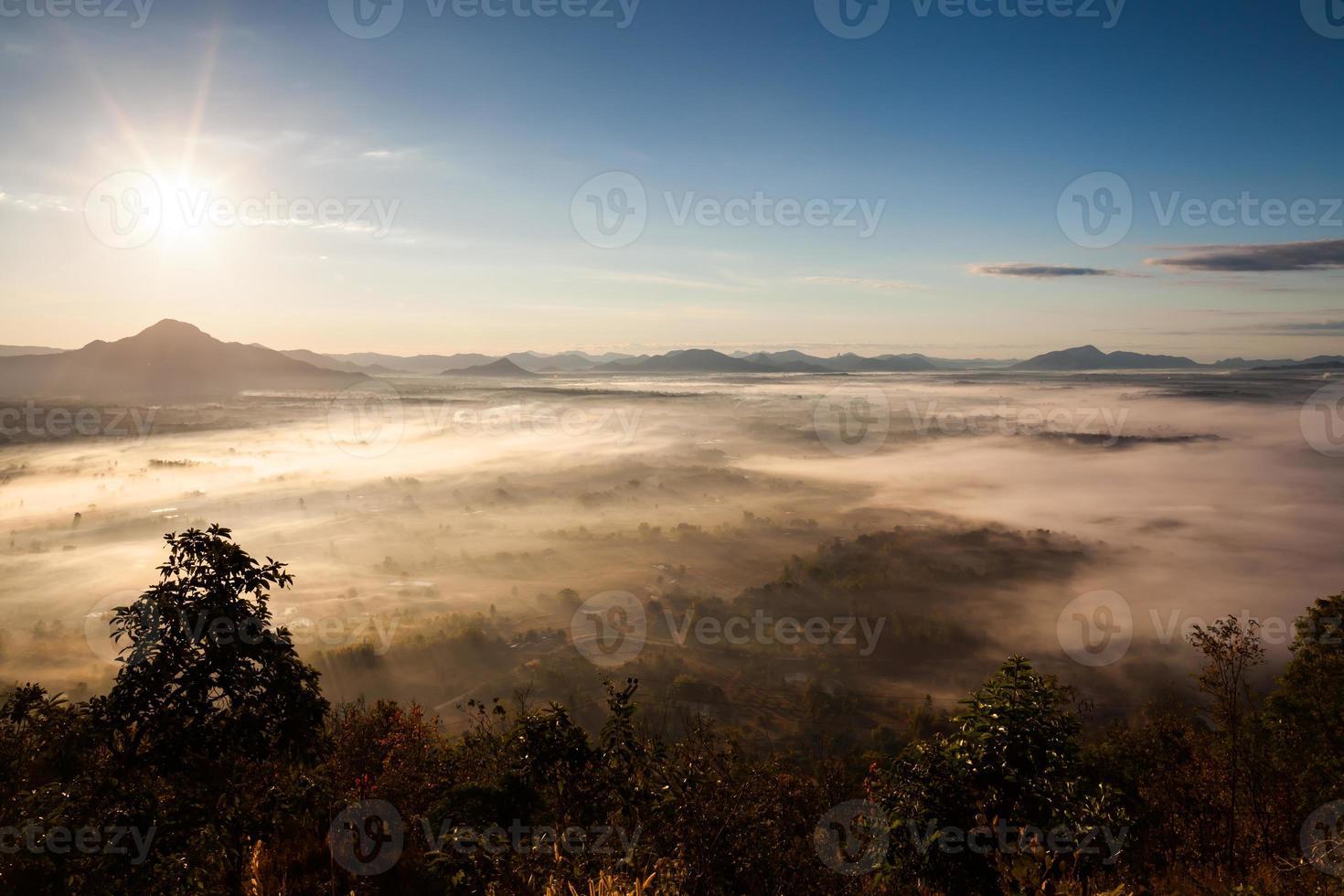 lever du soleil au-dessus d'un paysage de montagne brumeux photo