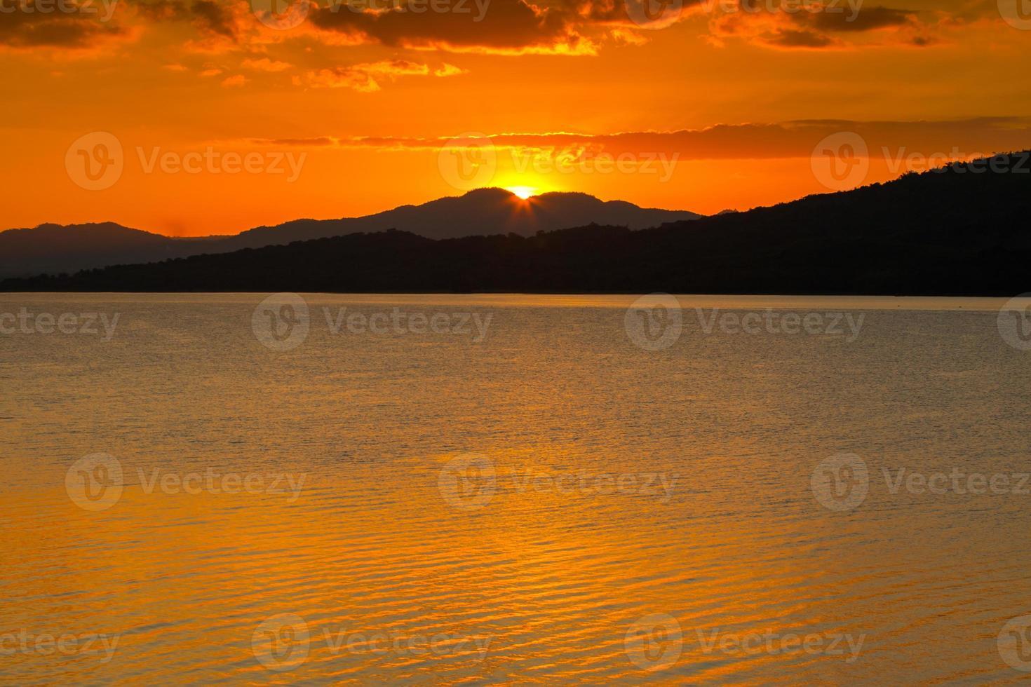 coucher de soleil orange vif sur les montagnes et l'océan photo