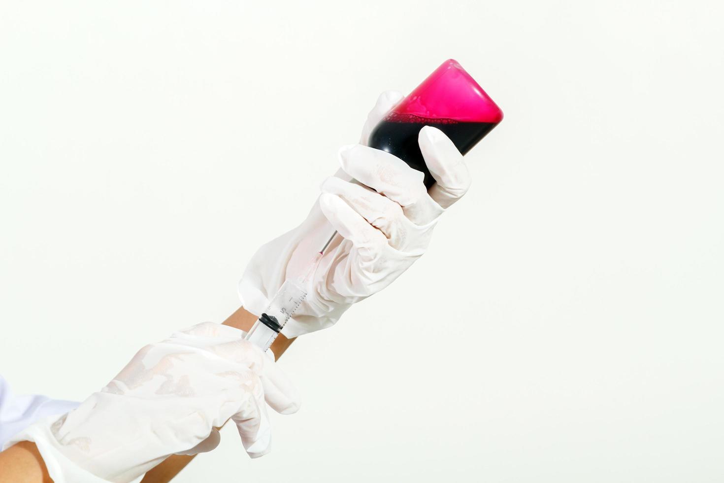 main gantée médicale tenant la seringue avec un liquide rouge photo