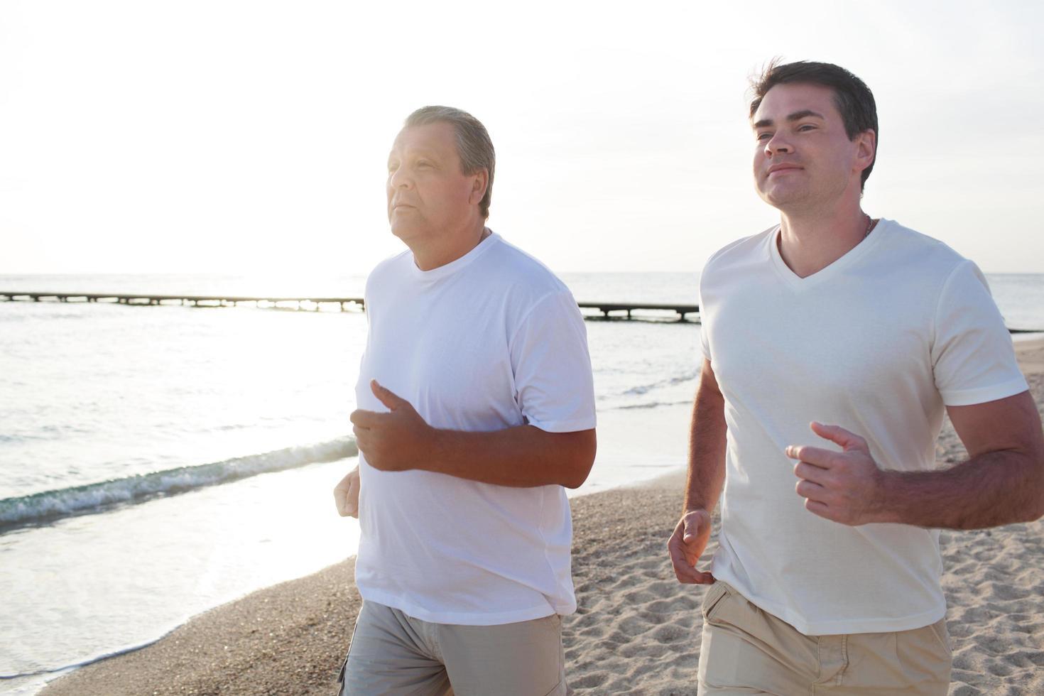 deux hommes courant le long de la côte en plein soleil photo