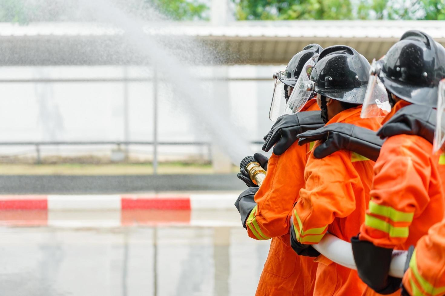 pompiers utilisant un extincteur et de l'eau du tuyau photo