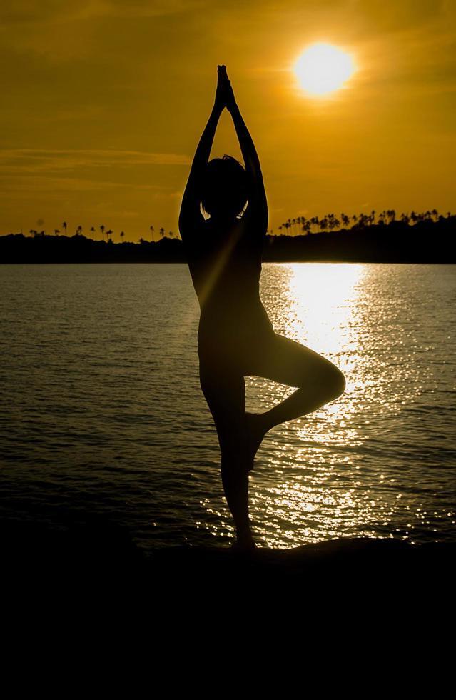 Portrait d'une jeune femme comme une silhouette au bord de la mer photo