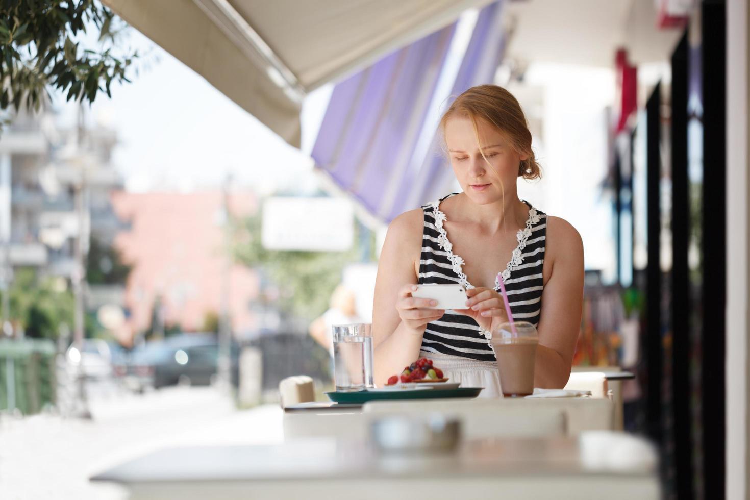 femme sur son téléphone dans un café en plein air photo