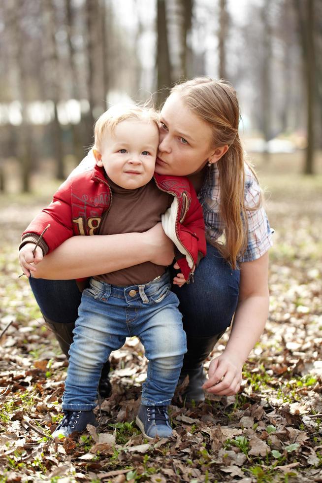 mère embrassant son fils dans un parc photo