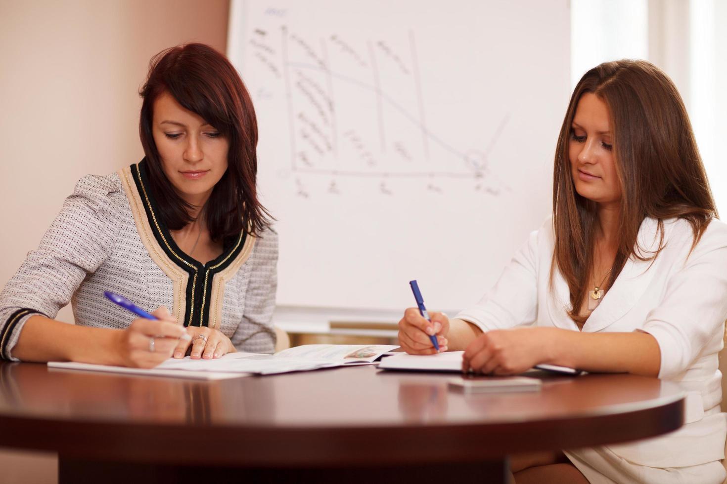 deux femmes prenant des notes lors d'une présentation commerciale photo