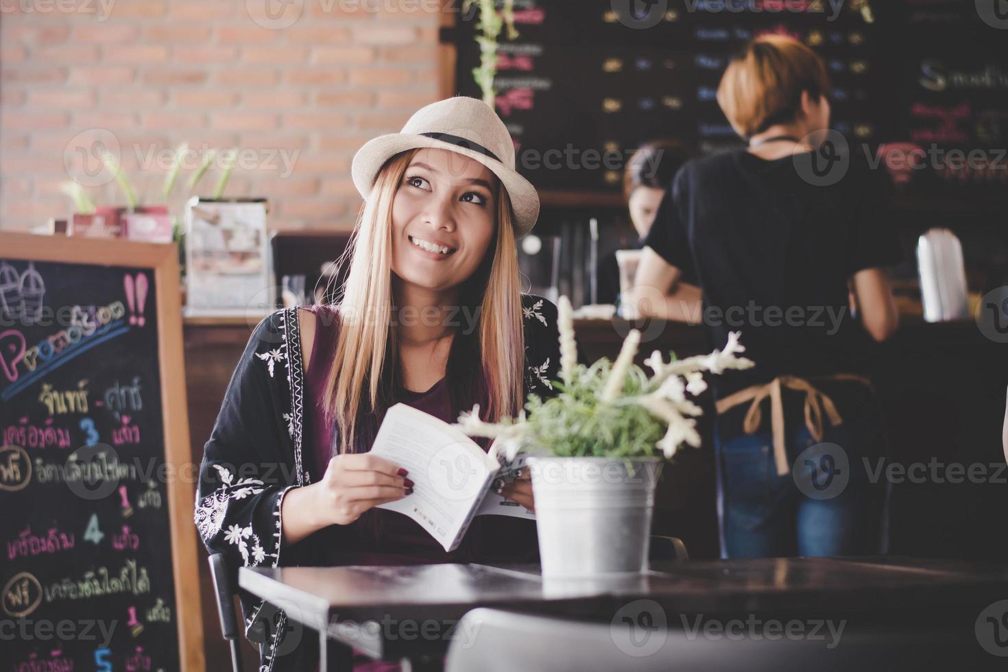 Happy business woman reading book tout en vous relaxant au café photo