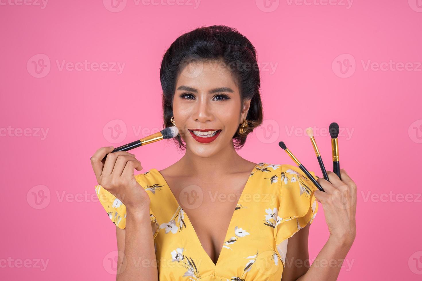 portrait d'une femme avec des pinceaux de maquillage photo