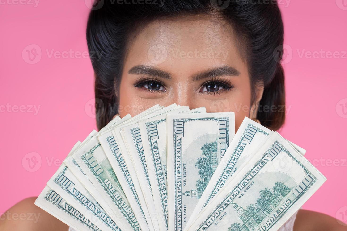 heureuse belle femme tenant des dollars photo