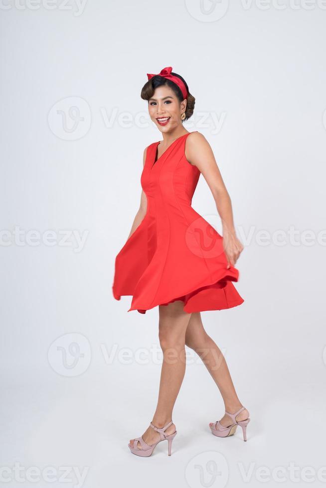 belle femme vêtue d'une robe rouge en studio photo