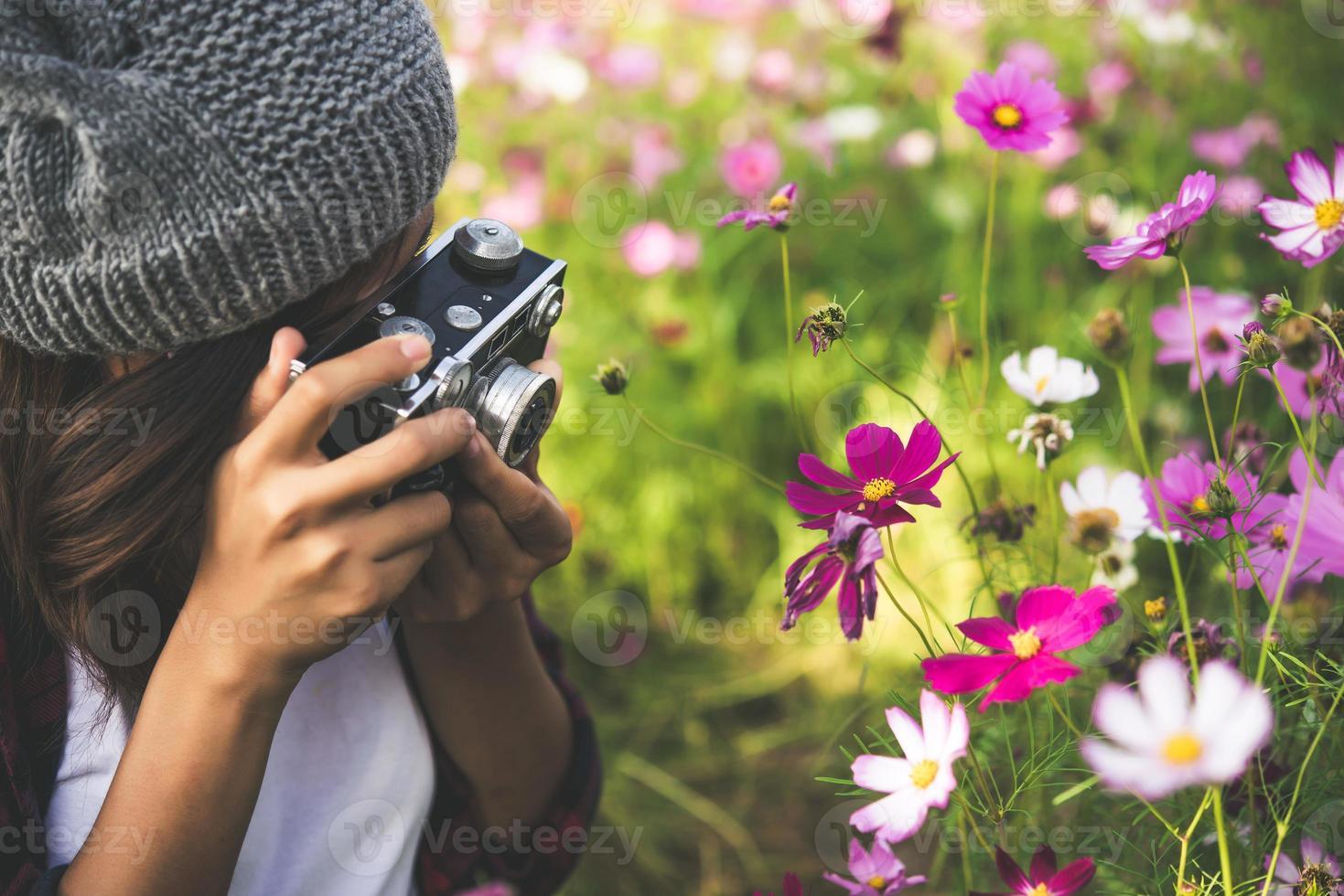 fille hipster avec mise au point de la caméra vintage tirant des fleurs dans un jardin photo