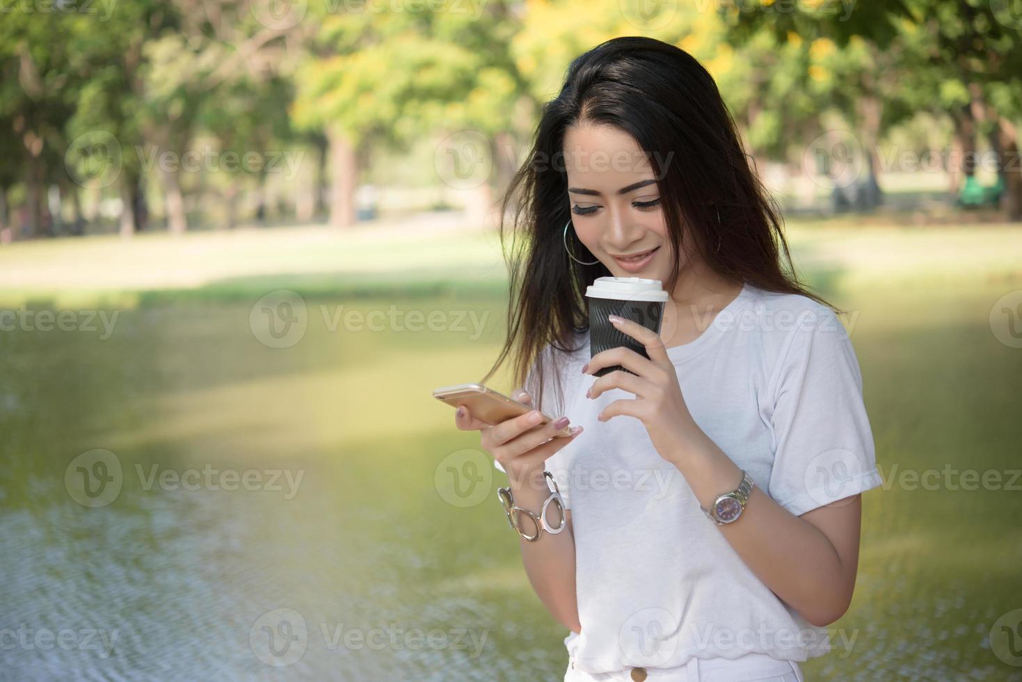 Jeune femme tenant une tasse de café tout en utilisant le smartphone à l'extérieur photo