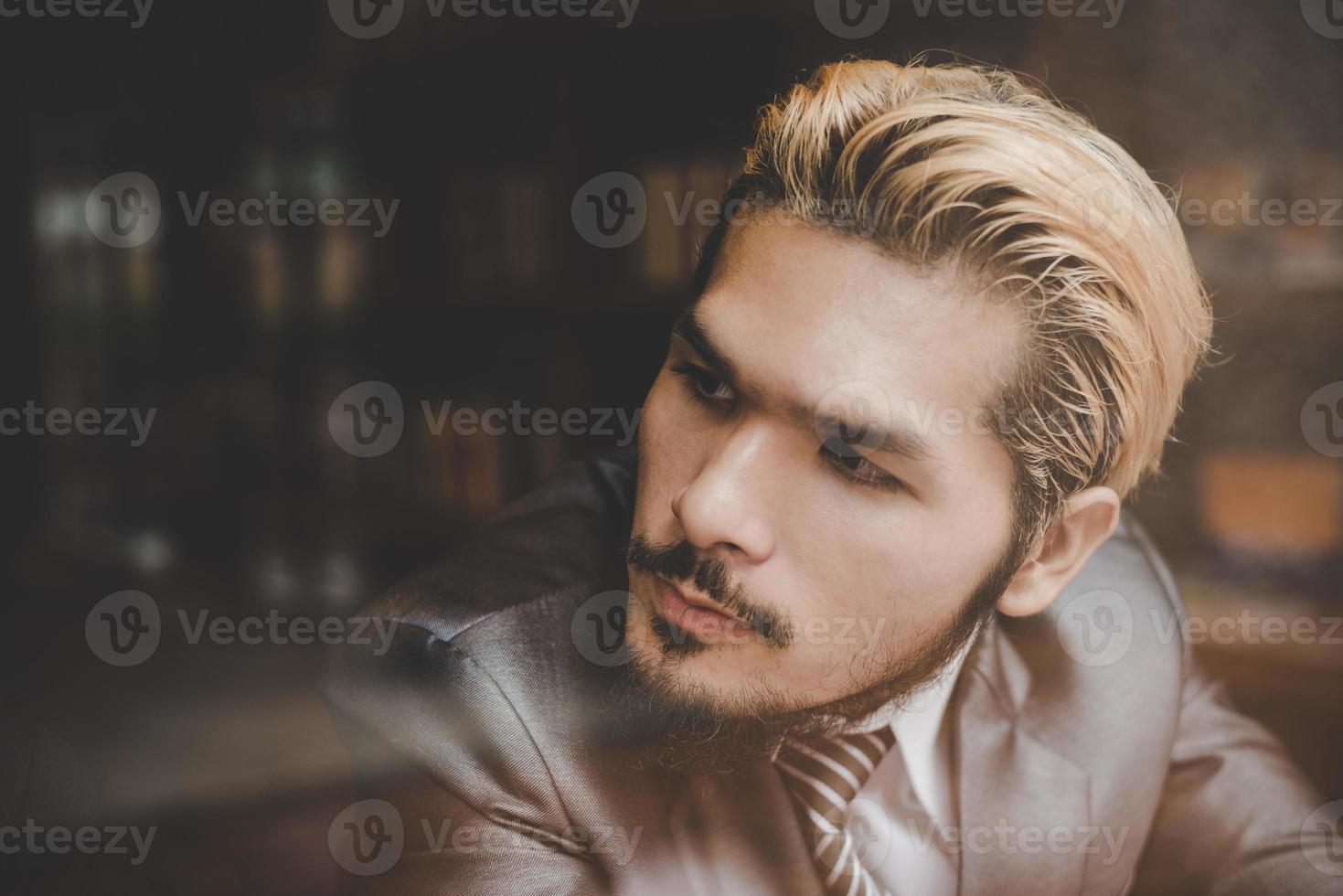 jeune homme d'affaires assis au café-bar, en détournant les yeux et en pensant photo