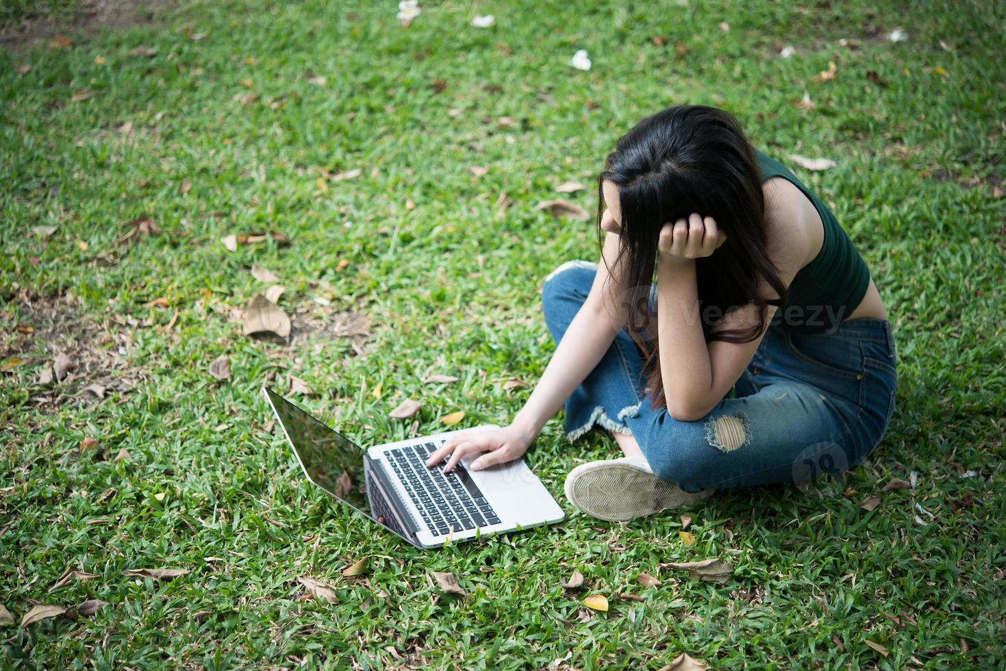 Belle jeune femme assise sur l'herbe verte et utilisant un ordinateur portable dans le parc photo