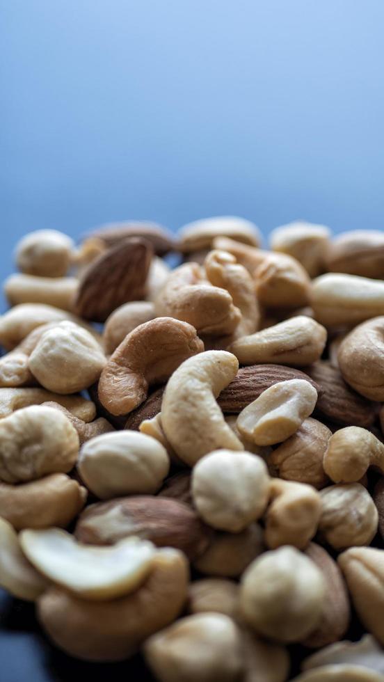 Tas de noix mélangées sur fond bleu photo