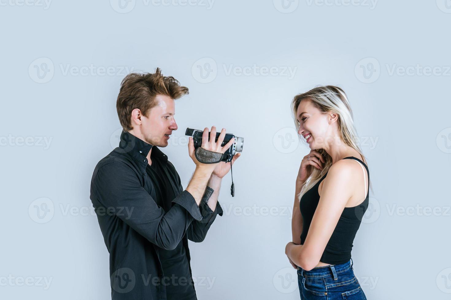 Heureux portrait de couple tenant une caméra vidéo et l'enregistrement d'une vidéo photo